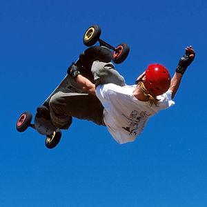 Jeune adolescent faisant un saut dans les airs avec sa planche à roulettes.