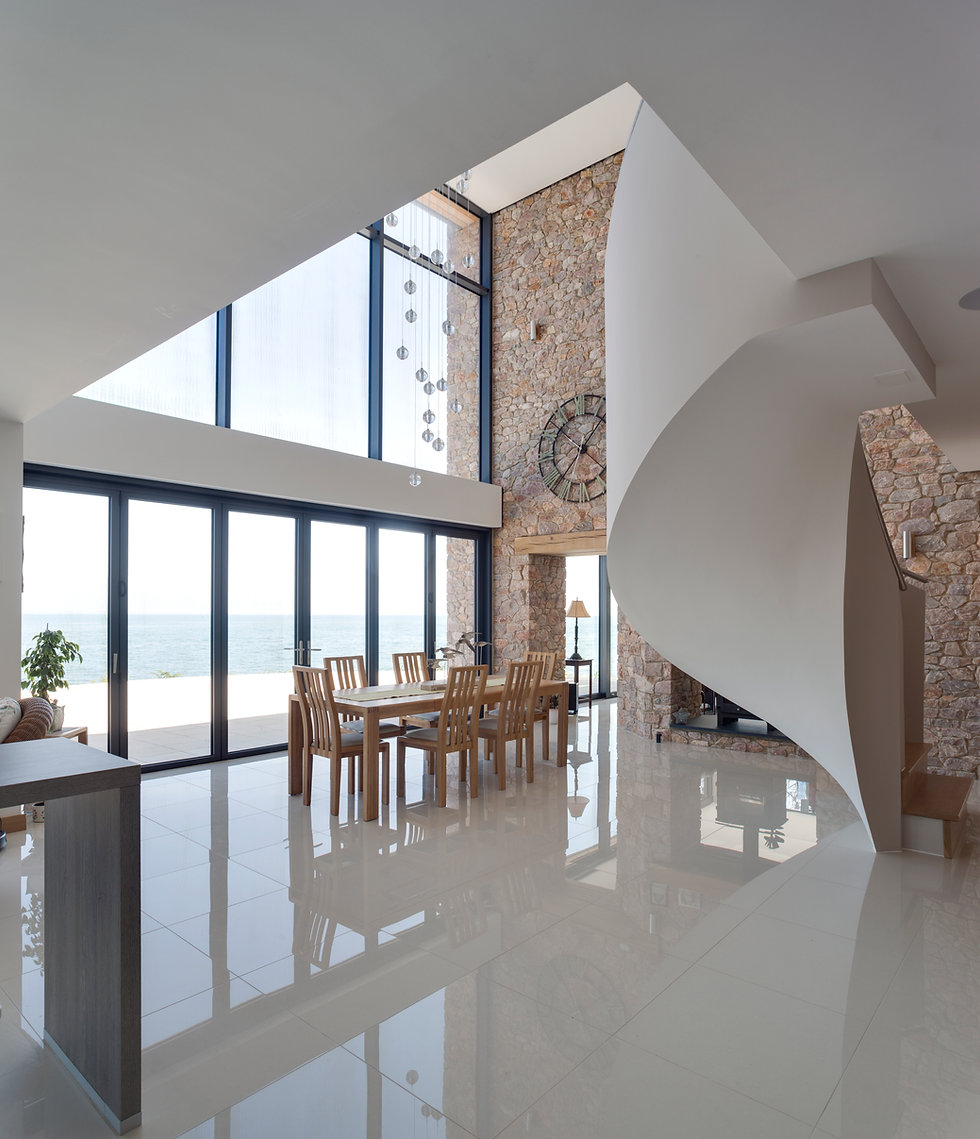 Open Plan Glazed Interior with Bespoke Spiral Staircase and Feature Stone Wall designed by MTA Chartered Architects Devon