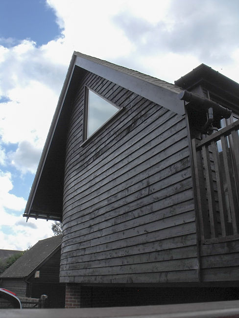 Hawkin Barn Conversion with Curved Horizontal Timber Cladding and Featue Gabl Window