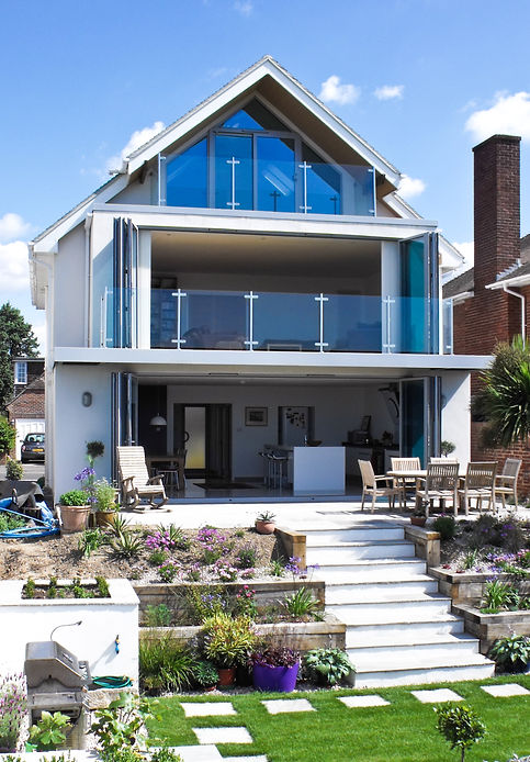 Fully openable gable elevation with glazed sliding folding doors and balustrade provide a sense of open plan between the main living space, the garden and beach beyond