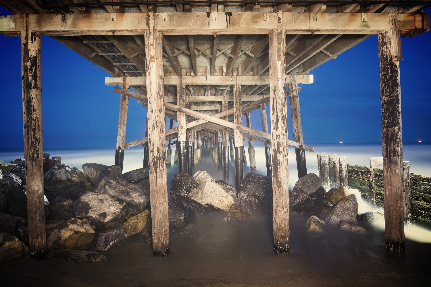 An image of the Balboa Pier in Orange County California early in the morning shows the structural de