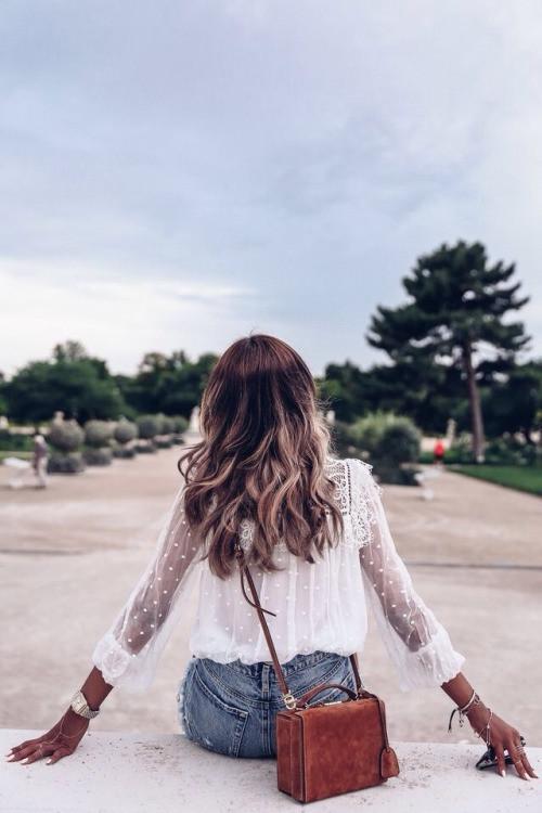 Mulher com short jeans, blusa branca e bolsa vermelha, sentada em um parque pensando sobre a lei da atracao