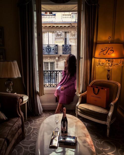 mulher rica sentada na janela de um hotel em Paris