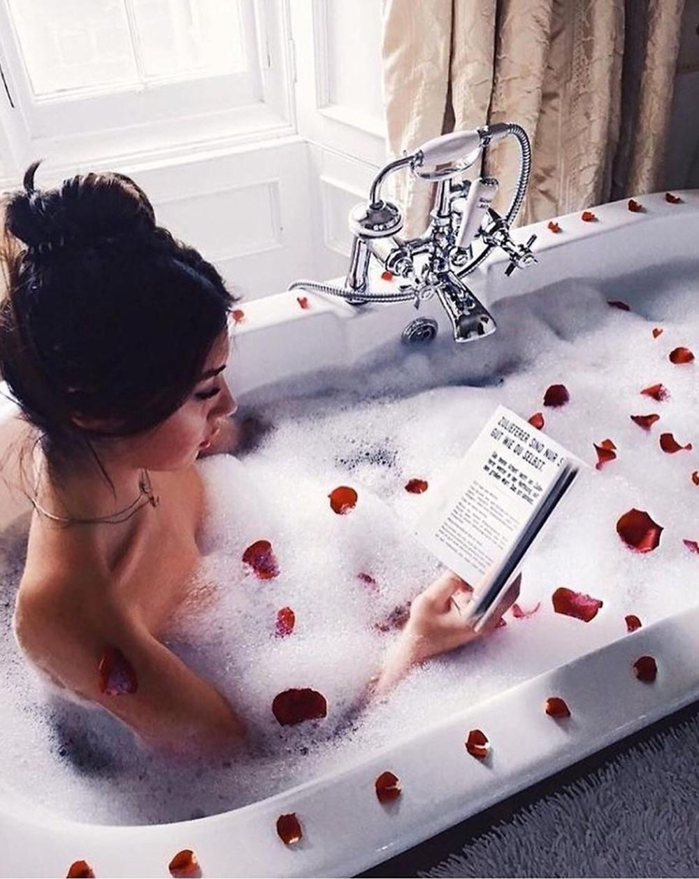 Mulher rica na banheira lendo sobre mentalidade milionaria