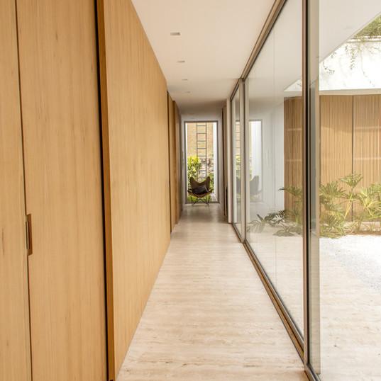 corredor que leva às 4 suites com piso em travertino toscano by camasa marmores & design