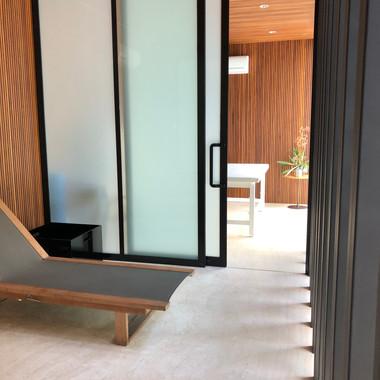 area relax com piso e bancada esculpida em travertino navona