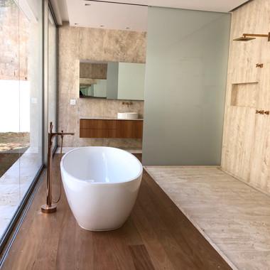 banheiro com piso e revestimento em travertino navona