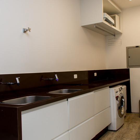 area lavanderia com piso em travertino toscano e bancadas em granito marrom absoluto by camasa marmores & design