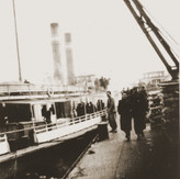 Jewish refugees from the Kladovo transport walk along a dock next to the Czar Nichola II riverboat.jpeg