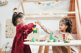 young girls playing with wooden blocks