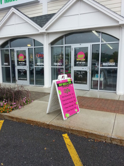 A frame sandwich board sign and window stickers in Falmouth, ME