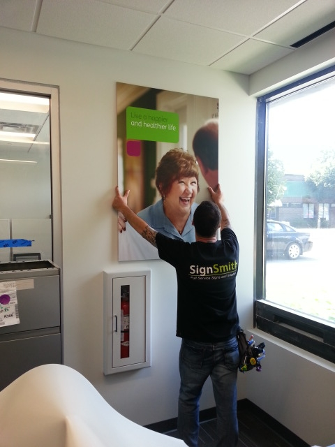 Installing interior poster sign on office wall