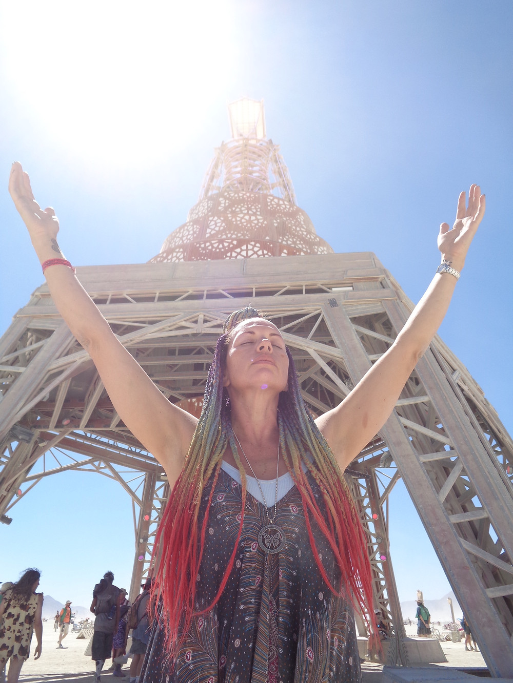 Woman raises hand above her head on sunny day at Burning Man in Black Rock City.