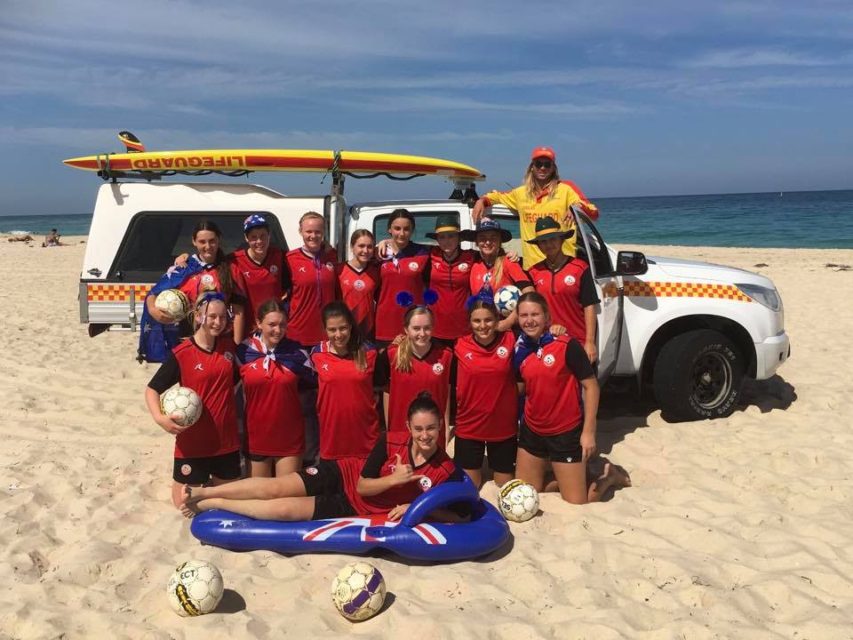 Picture of junior soccer players at a beach with lifeguard in the background