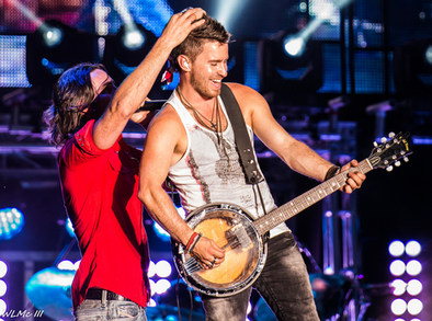 Derek performing ganjo on stage with Jake Owen