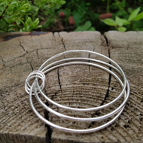 Silver bangles linked with circles.