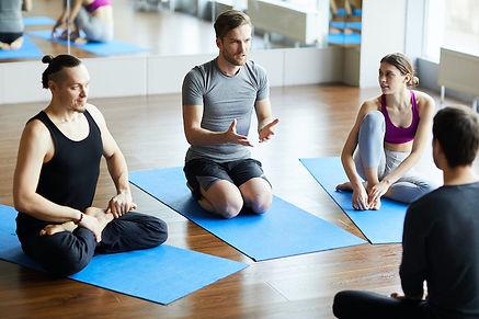 young-man-asking-question-at-yoga-semina