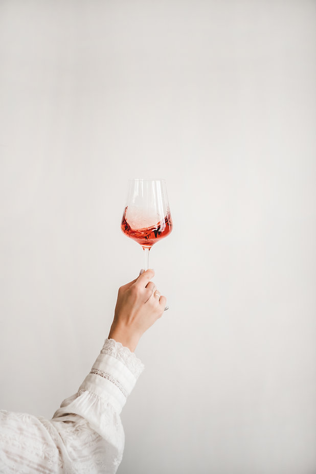 Womans hand in white shirt holding glass of rose wine over white wall background. Wine sho