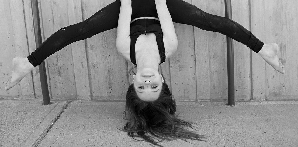 female dancer hanging upside down on ballet barre