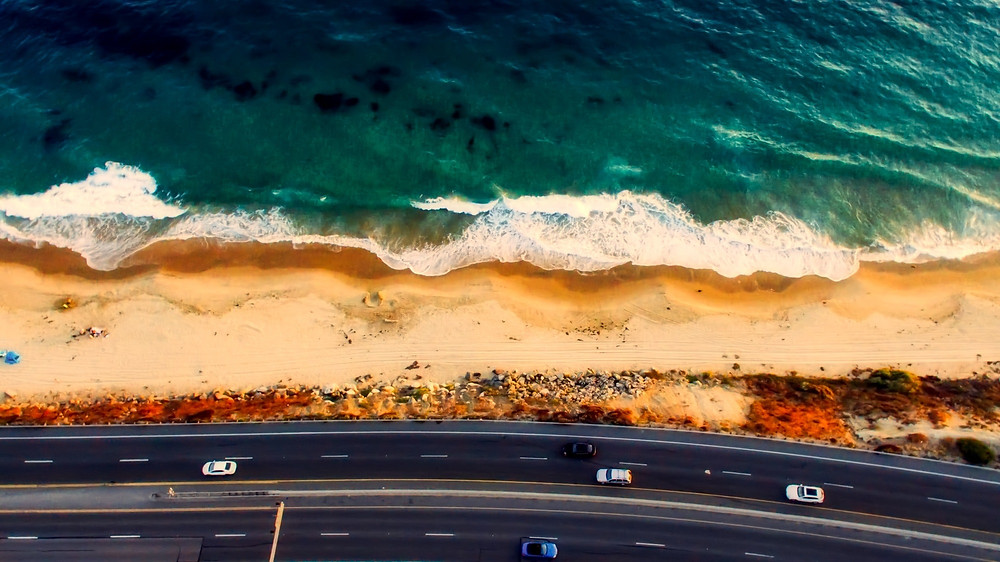 Aerial view of a highway running close to pounding surf.