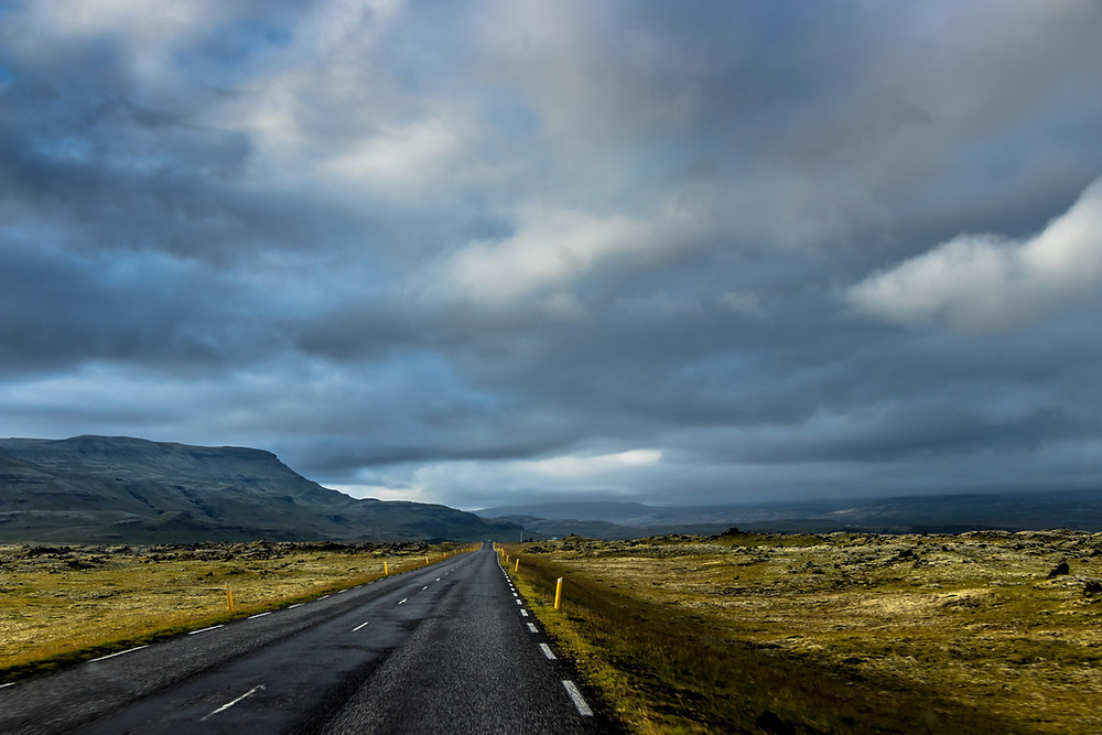 State highway running to the horizon under threatening clouds