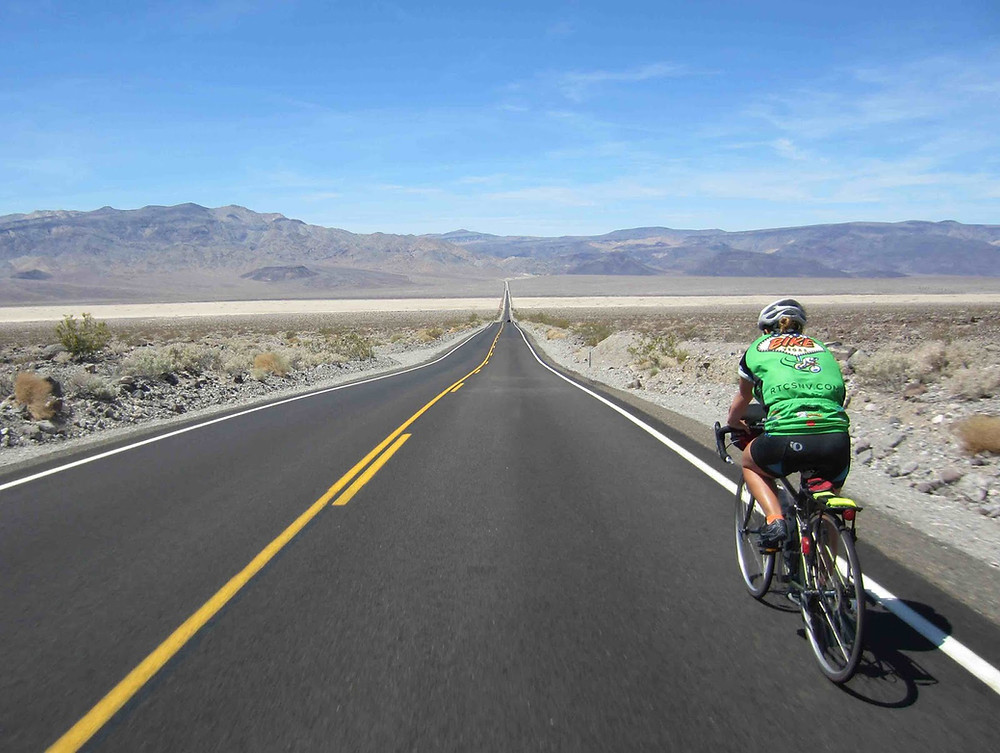 Wide shot of cyclist riding across Death Valley