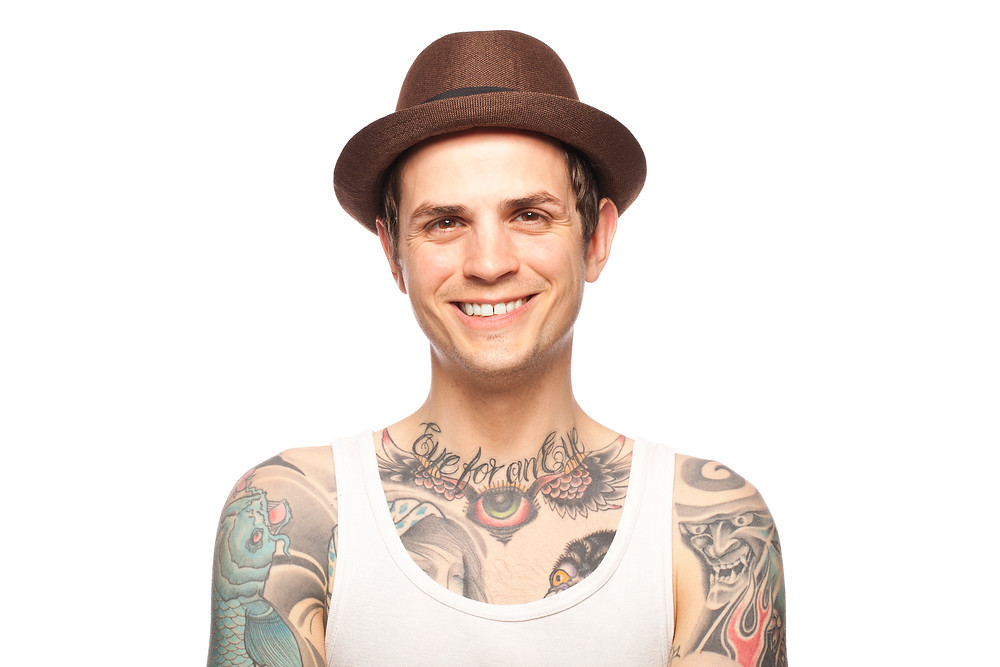 Tattooed man wearing a fedora.