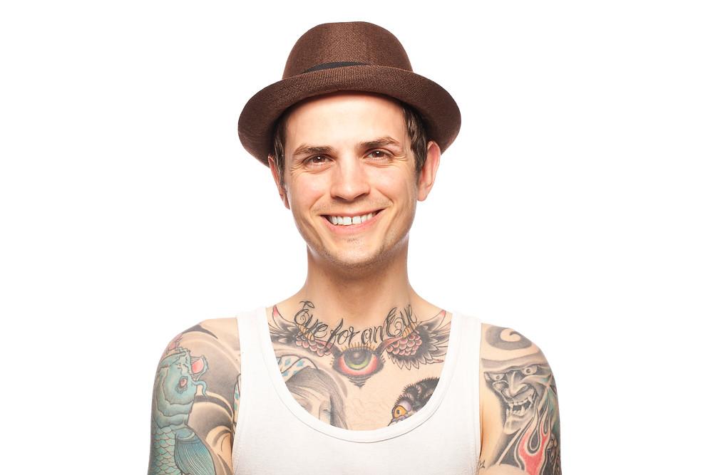 Tattooed man wearing a fedora.