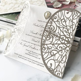 Classic white laser cut wedding invitations with a teardrop pearl & diamanté embellishment.jpg