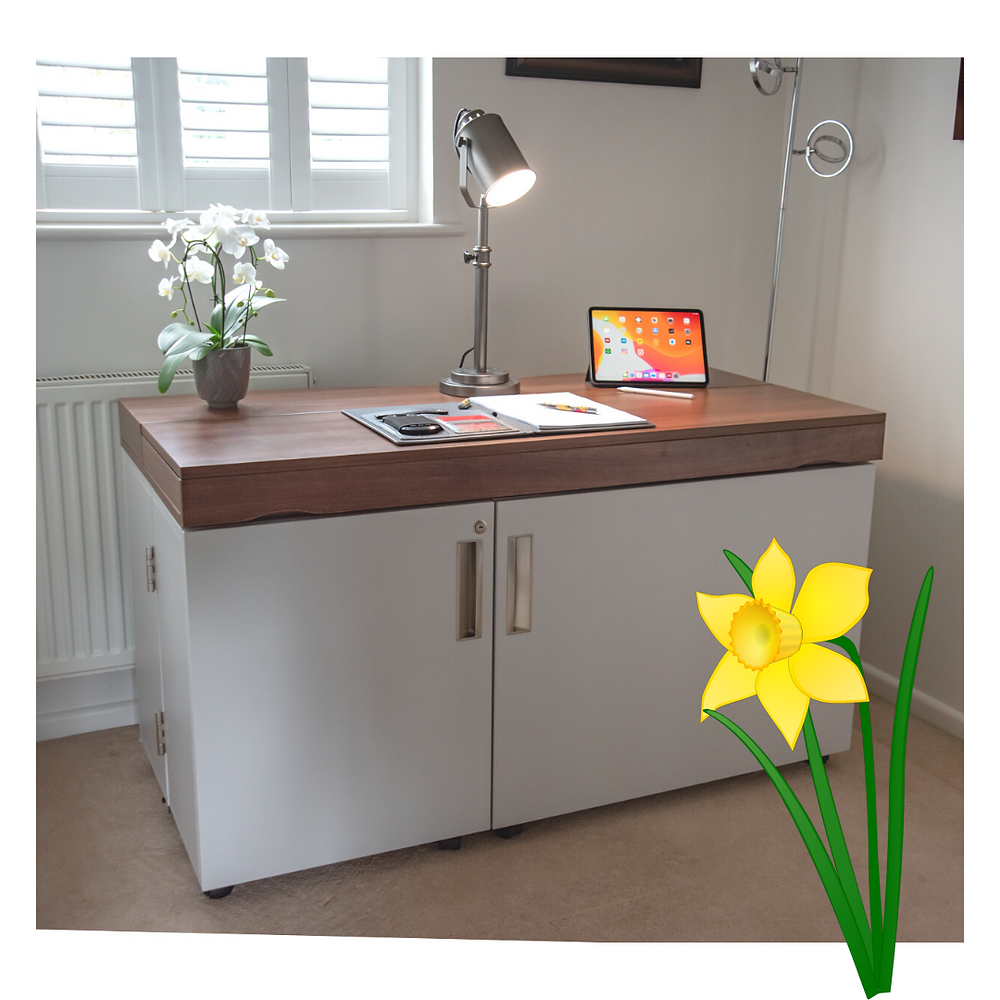A stylish home desk folded up with a lap top, papers and an orchid on top