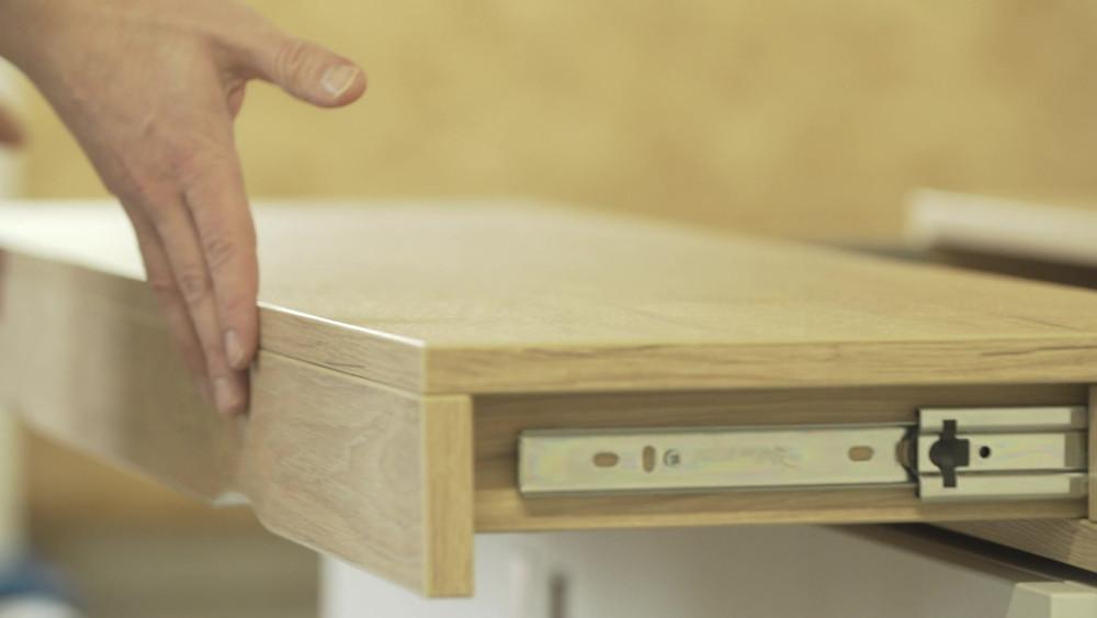 Man sliding the desk top shut of a stylish home desk