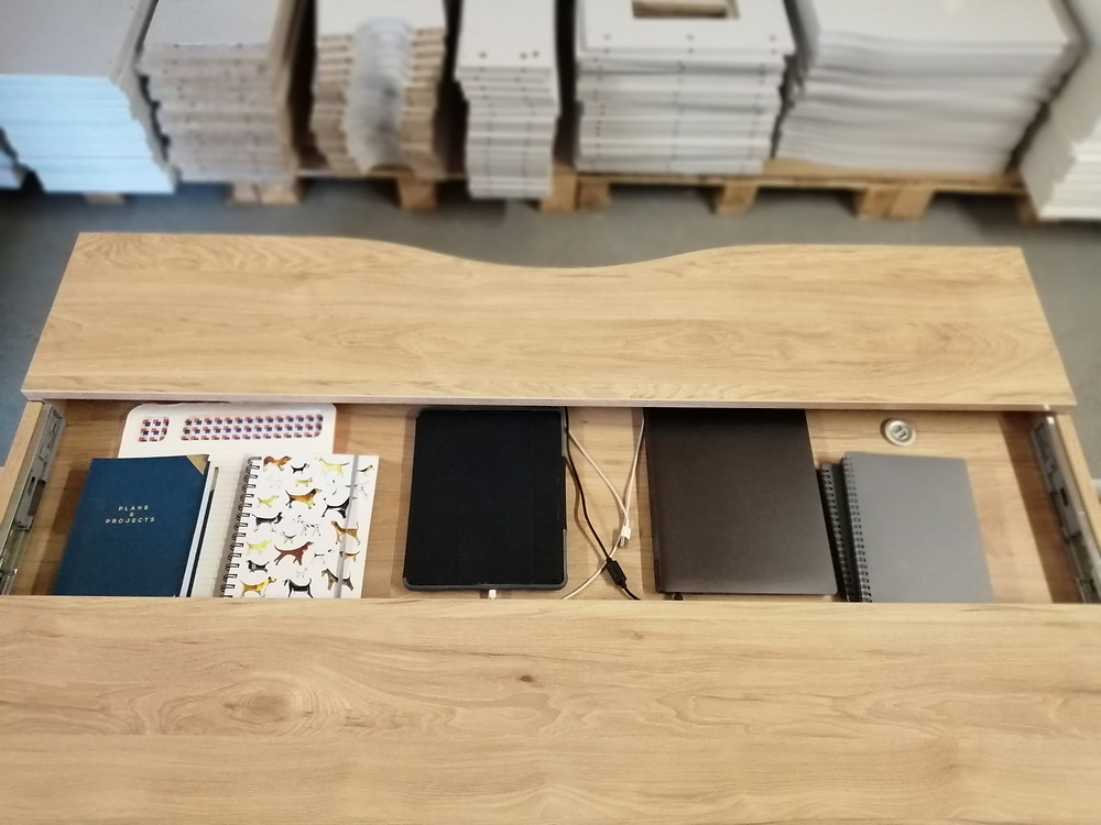 a stylish home desk with the sliding desk top open to reveal note books, laptop and tablet