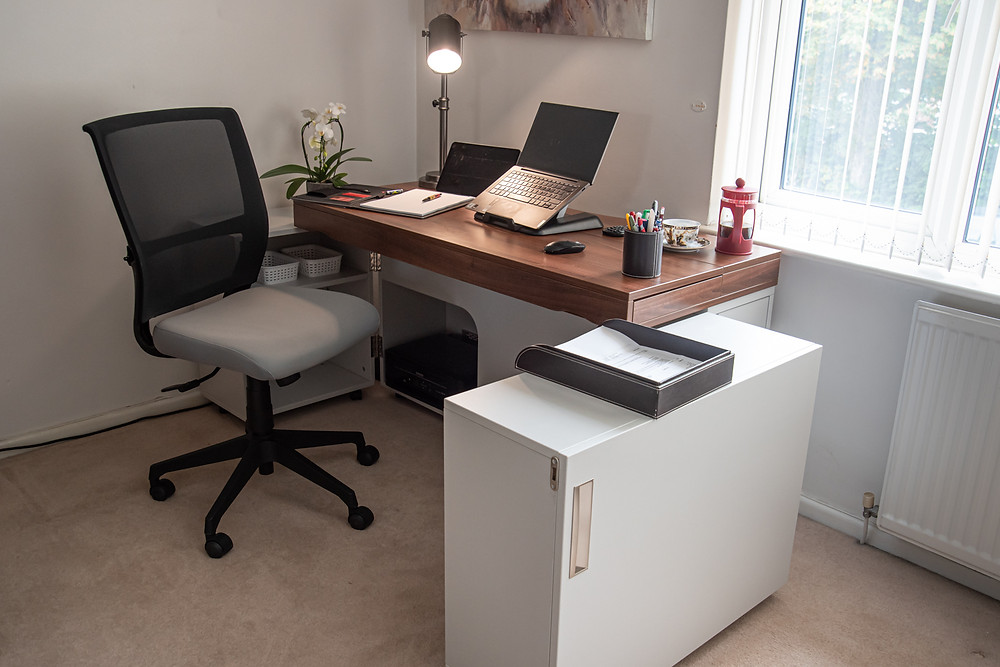 A stylish home desk with the doors opened out. Lap top on top and other office essentials