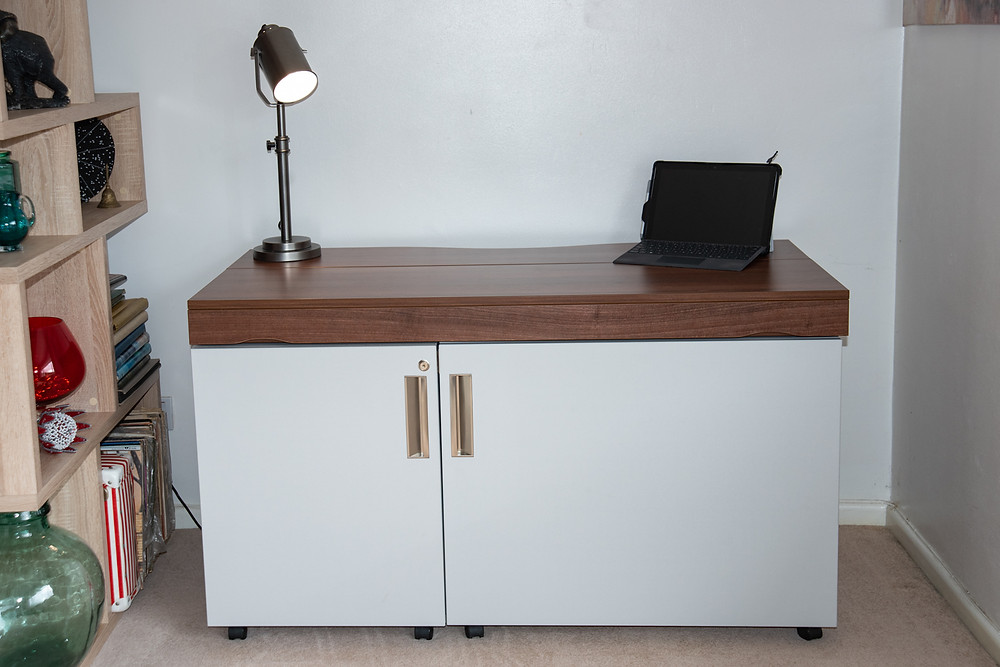 A foldable home working desk, closed up with a lamp and a tablet on the top