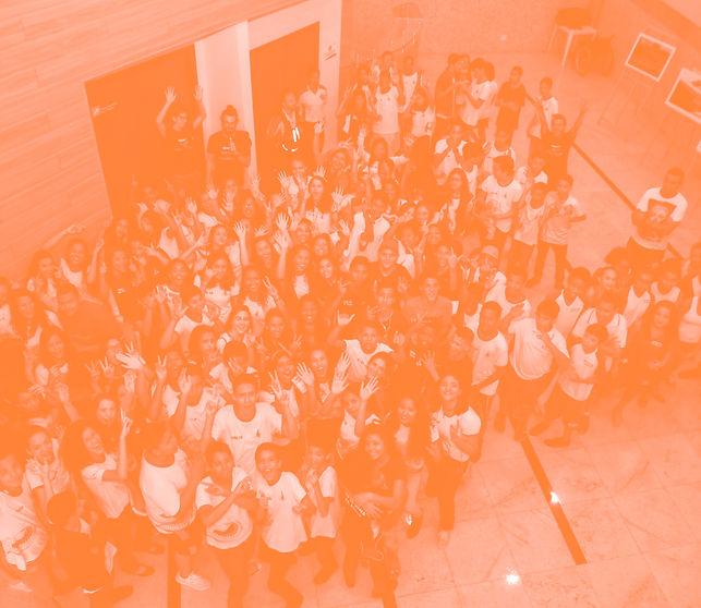 grupo de alunos acenando felizes na porta do teatro
