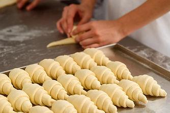 Baker making croissants