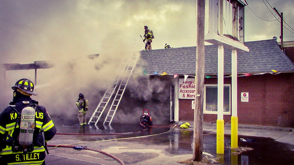 Firefighters work at a fire in a strip mall.