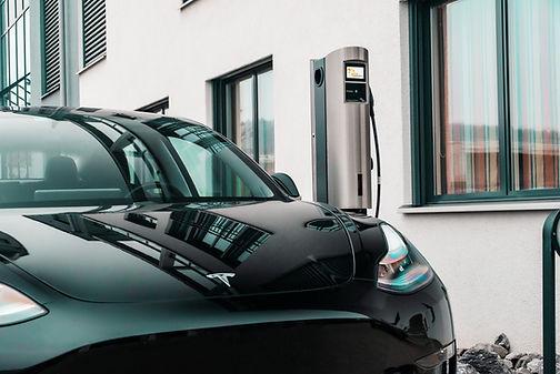 Tesla Model 3 neben dem Juice Charger 2 Elektroauto Wandladestation mit Stele