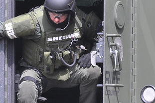 SWAT team membe exiting small space with vest
