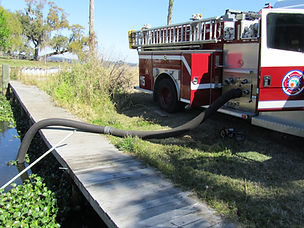 fire engine syphoning water wih hose