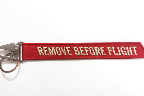 Chaveiro Remove Before Flight grande com mosquetão