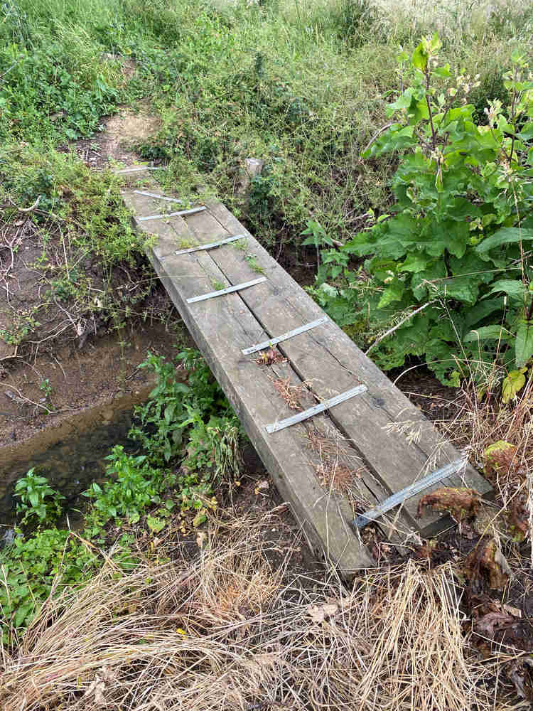 A dodgy footbridge consisting of 2 rolling sleepers badly fastened together