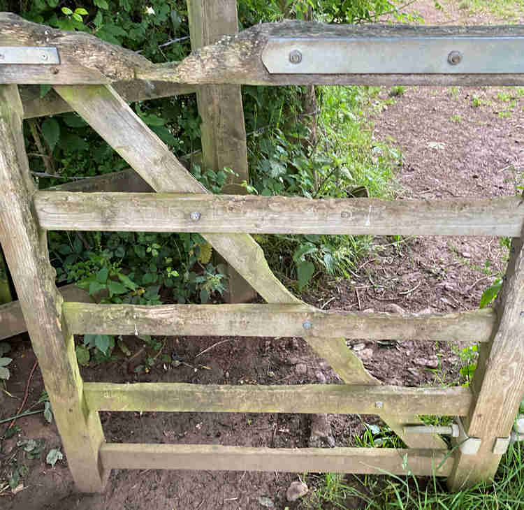 A gate with an incredibly worn top bar, were the hand rests