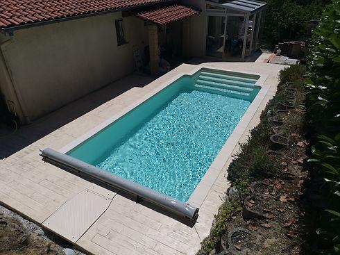 Terrasse en bois et margelles. Installation de volet roulant. Liner clair et marches dans la piscine.