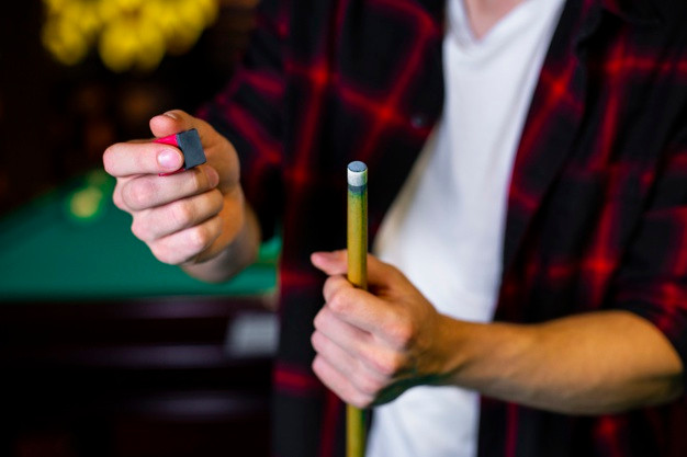 close-up-guy-with-pool-cue-chalk_23-2148