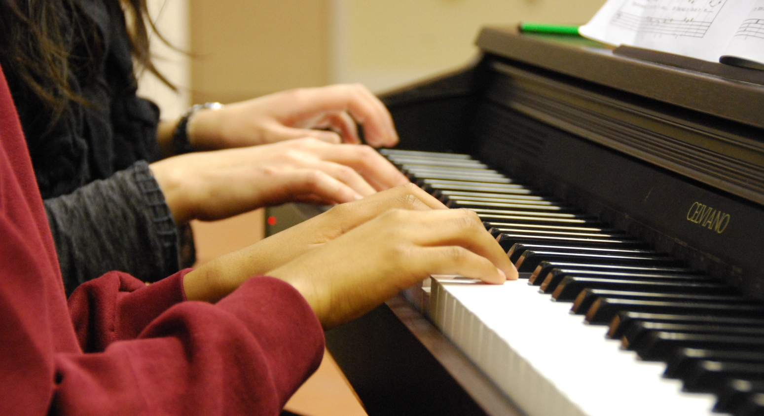 teacher and student hands on piano