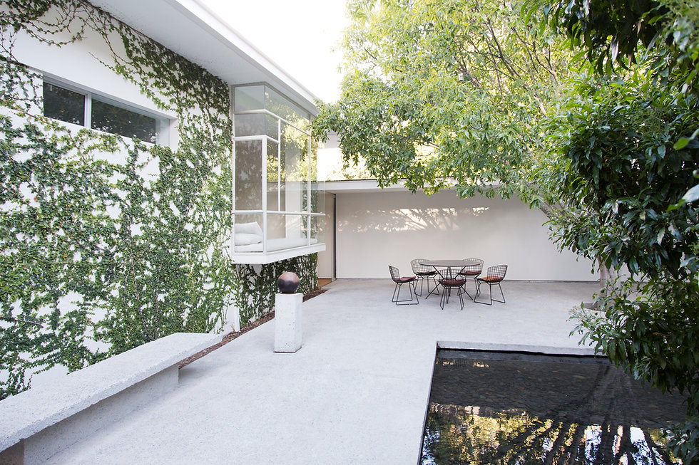 Concrete Porch, outside dining area for BBQ's and barbaques.  high end designer, luxury, paving and designed by landscape architects.  Moderm minimalist garden features with ivy and trees.