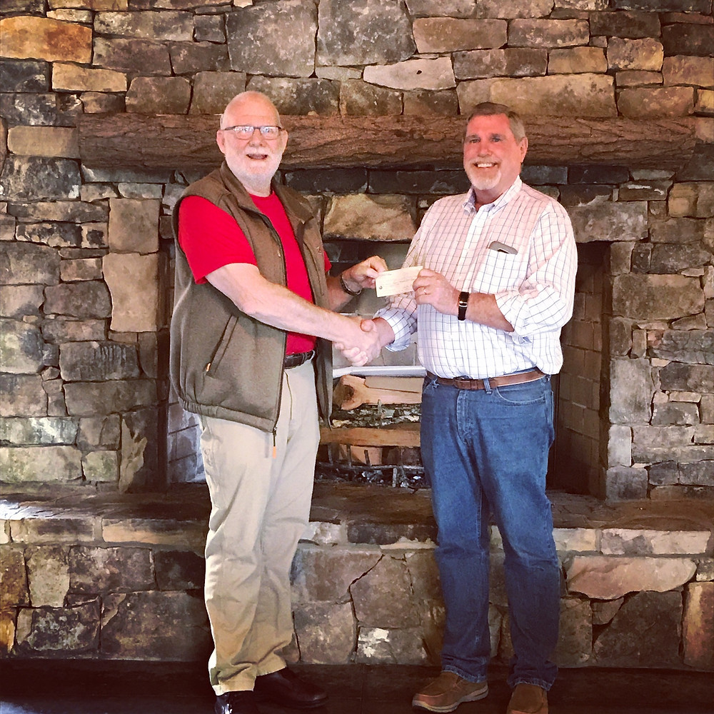 Rhapsody President Rocky Ford presents a check to Habitat Rabun President Dan McAfee for $60,000