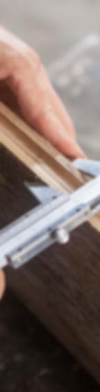 A picture framer holding a vernier caliper measuring an award frame.