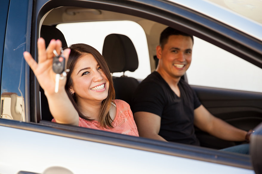 Couple in car, holding new key fob.